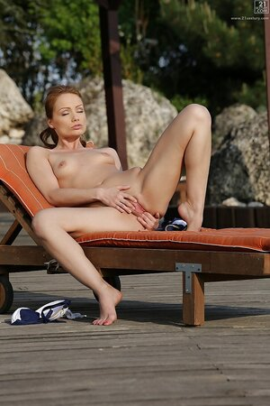 MILF Sophie Lynx gets comfortable on the lounger and rubs pussy with fingers