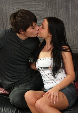 Boy unclothes black-haired girlfriend and stretches her cunny on leather couch