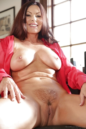 Mature pornstar demonstrates big breasts and hot intimate haircut on the chair