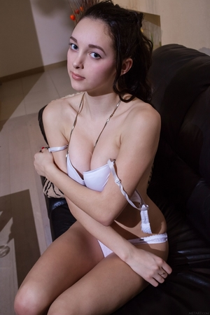Asian cutie enters the room and gets snow-white lingerie off on the black couch